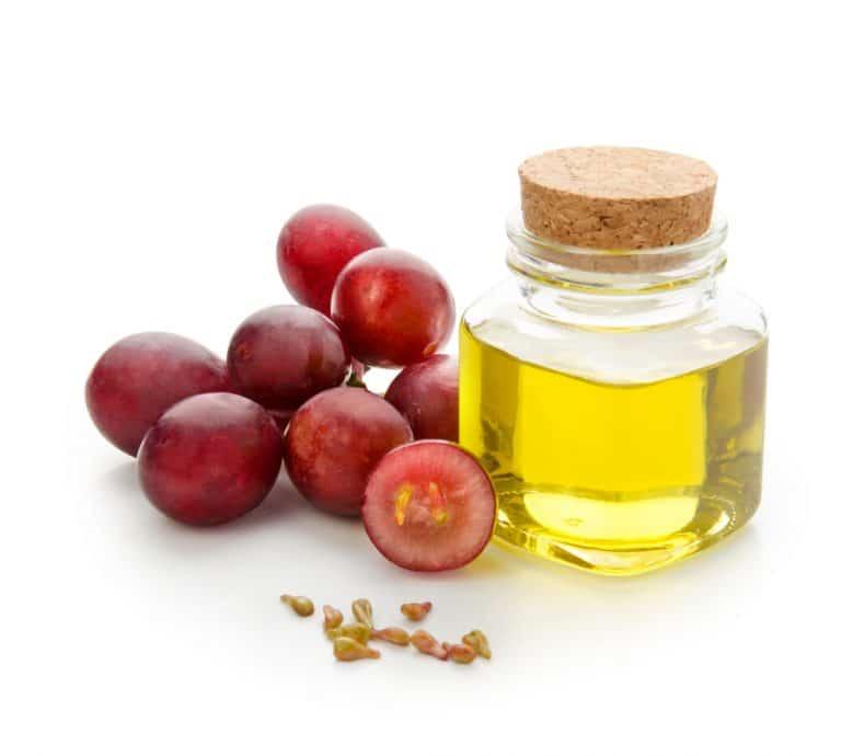 Aceite de uva en un frasco  y uvas
