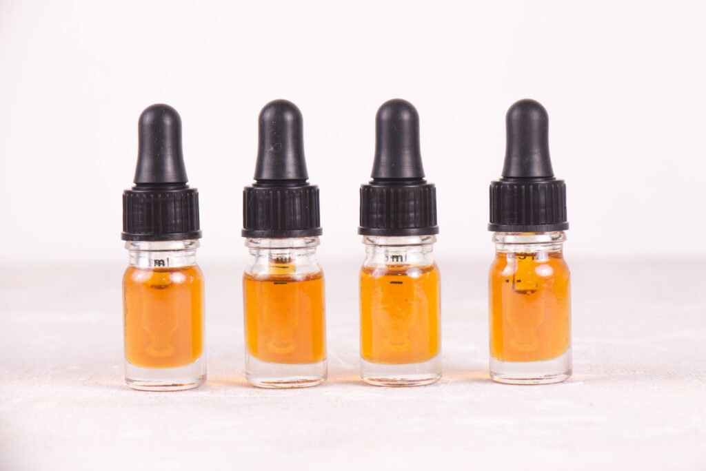 Detalle macro de gotero con aceite CBD, extracción de resina viva de cannabis aislado sobre blanco - concepto de marihuana medicinal